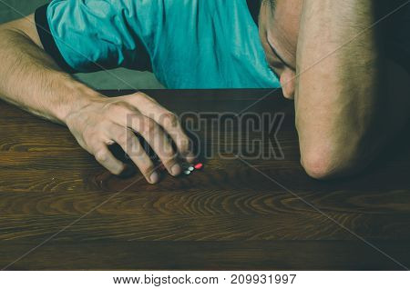 Depressed man suffering from suicidal depression want to commit suicide by taking strong medicament drugs and pills