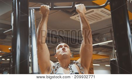 Bodybuilder in the gym performs pull up - close up view