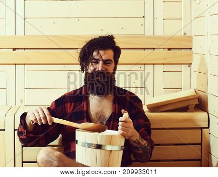 Handsome cheerful man or bather bearded hipster with beard and moustache in red checkered shirt pours water with spoon from bucket in sauna thermal bath on wooden background