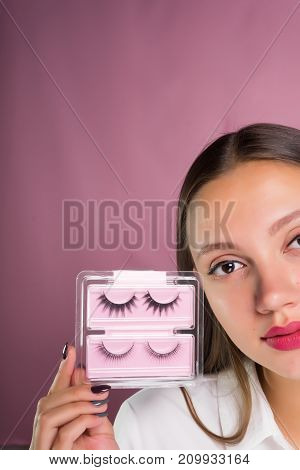 young beautiful girl holding a package of black false eyelashes