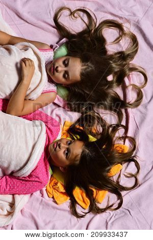 Girls Lie On White And Pink Bed Sheets