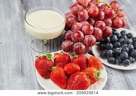 Strawberry blueberry with yogurt and grapes on wooden background