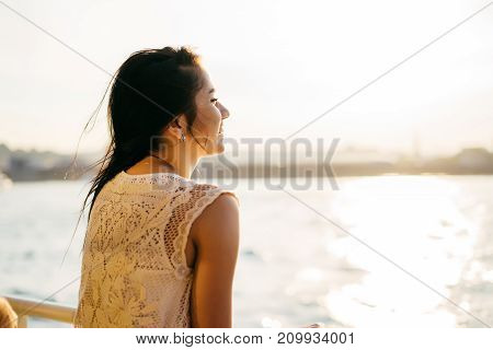A girl enjoying the sunset during a boat trip. Back view