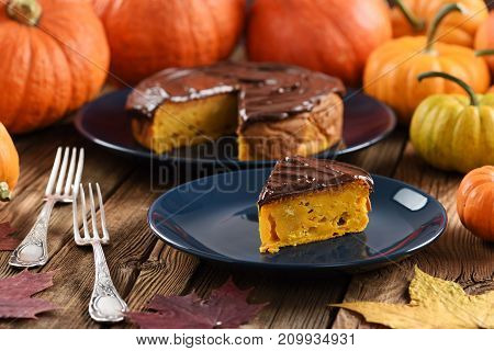 Pumpkin dessert. Delicious pumpkin cake with chocolate icing served with small bright orange pumpkins and marple leaves closeup