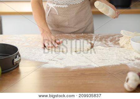 Female hands making dough for pizza or bread while using rolling pin. Baking concept.
