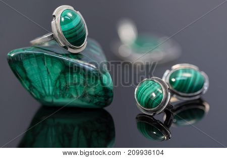 Closeup beauty silver earrings and ring with malachite on malachite stone piece on black acrylic desk.