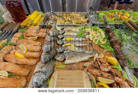 Dry and salt fish herring or other with lemon and salat ready on the restaurant big table.