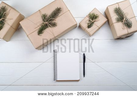 Top view of blank notebook for template design on white wooden background with xmas decorations copy space. Christmas background with notebook for wishlist or to do list gift boxes with fir branches