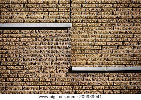 The closeup of a clinker facade of rough stones on the facade of a building.