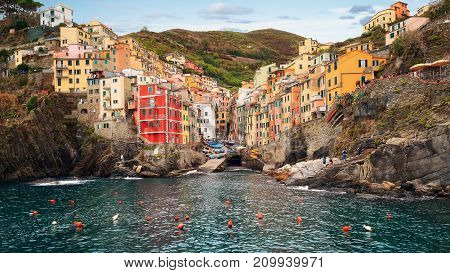 View of Riomaggiore by day. Riomaggiore is a small town in the province of La Spezia in Liguria northern Italy. It is part of the Cinque Terre park UNESCO World Heritage Site.