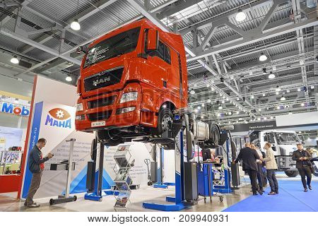 MOSCOW, SEP, 5, 2017: Maintenance equipment, repair tools and special devices for trucks. Red MAN truck lifted on special car lift elevator hoist on Commercial Transport ComTrans-2017. Truck MOT