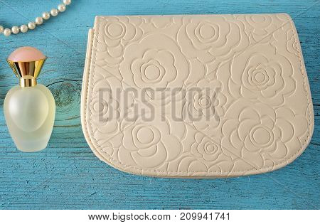 A handbag and a bottle of perfume on a blue wooden background. View from above.Flat lay.