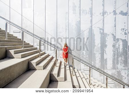 Business woman in red dress on the big stairway on the grey wall background