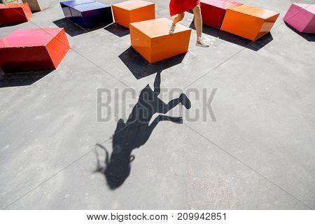 Shadow of a jumping woman on the ground with colorful boxes