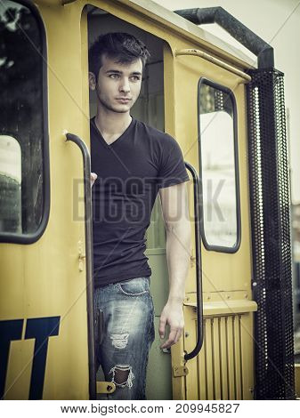 Close-up portrait of handsome young man outside on old yellow train, looking away