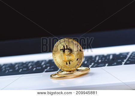 Bitcoin coins on a keyboard of white laptop. Computer. Investment situation. New virtual currency. Most valuable cryptocurrency