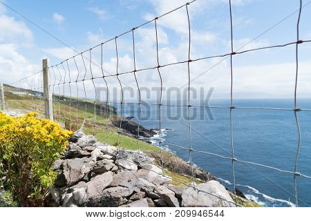 Wire mesh fence along low rock wall above rocky cliffs along Wild Atlantic Way dramatic and scenic tourist route County Kerry on Irish west coast