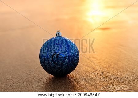 Closeup of Blue Christmas Ball at the Beach at Golden Sunset Winter Holiday Concept