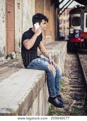 Attractive young man sitting on railroad, calling somebody on cell phone, wearing black t-shirt and jeans, looking afar