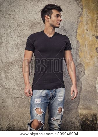 Smiling young man standing against concrete wall. Looking away