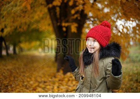 Happy Little Is Girl Playing In Beautiful Autumn Park On Warm Sunny Fall Day. School Holidays.
