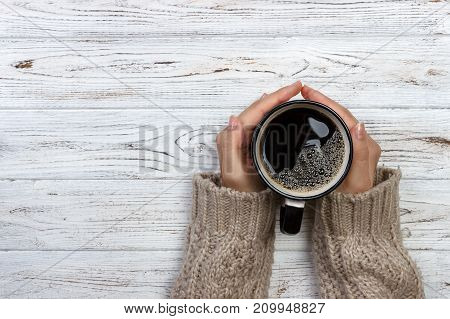 Woman holding cup of hot coffee on rustic wooden table closeup photo of hands in warm sweater with mug winter morning concept top view.