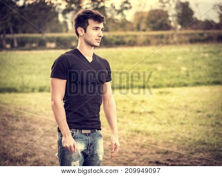 Attractive, fit young man relaxing standing on lawn in the countryside in the grass, looking away