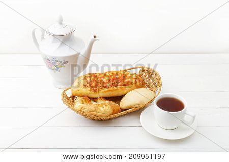 Wicker basket with fresh pastry teapot ant cup of tea on white wooden table.