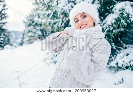 Smiling woman in cozy knitting pullover and fur hat stay om winter forest glade