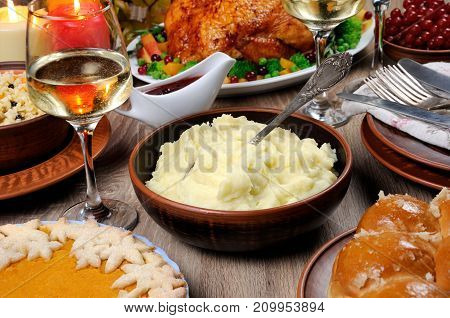 A bowl of mashed potatoes on a table among the pumpkin pie baked turkey cranberry-orange sauce a glass of white wine for Thanksgiving