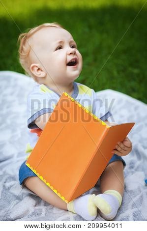 little baby reading interesting book in city park, handsome kid resting in garden with his book