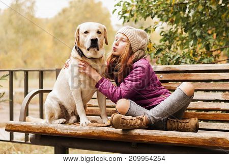 Portrait of a beautiful girl with her dog while walking in the autumn park