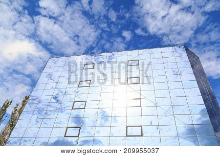 Blue clouds and trees are reflected in the glasses of windows of a modern building. Bottom view