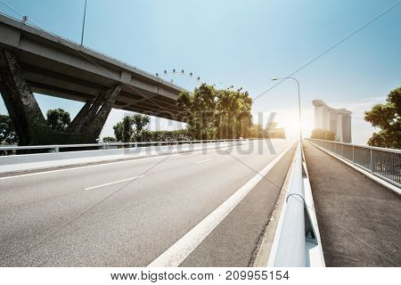 traffic on road near elevated road in blue cloud sky