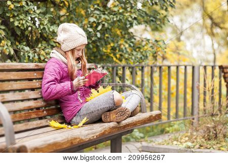 Young stylish hipster girl sitting on the bench in the autumn park and reading book