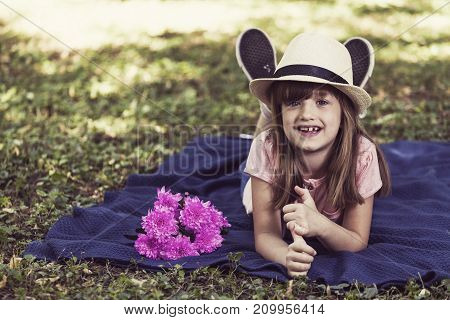 Pretty Little Girl Is Lying On A Blanket In The Park