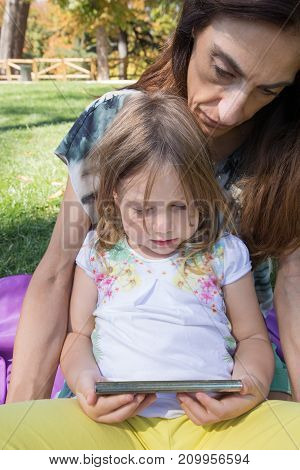 Little Girl And Woman Watching Mobile Sitting In Park