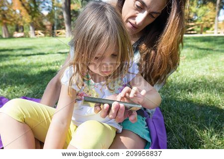 Little Girl Touching Mobile Screen Of Woman Sitting In Park