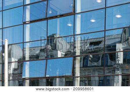 Reflection of an old building in a modern glass facade contrast of urban architecture blue sky in hamburg on a sunny day