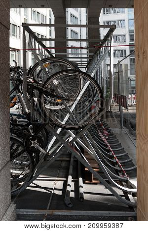 vertical bicycle rack construction of metal saves space for parking bikes in the city