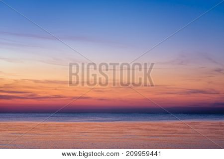 Horizontal picture of clouds in the sky above calm sea surface during sunset