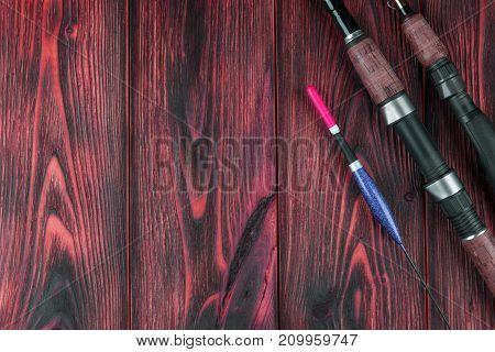 Fishing tackle - fishing rod fishing float and lures on beautiful red wooden background