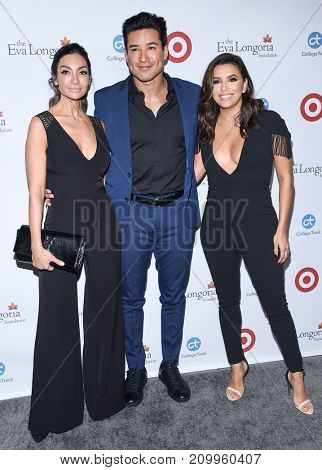 LOS ANGELES - OCT 12:  Eva Longoria, Mario Lopez and Courtney Laine Mazza arrives for the Eva Longoria Foundation Dinner on October 12, 2017 in Beverly Hills, CA