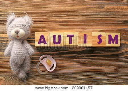 Cubes with word AUTISM and toy on wooden background