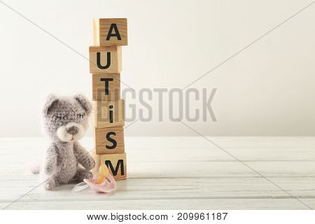 Cubes with word AUTISM and toy on wooden table