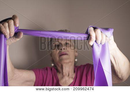 Senior Woman Doing Rehabilitation Exercises With Elastic Band