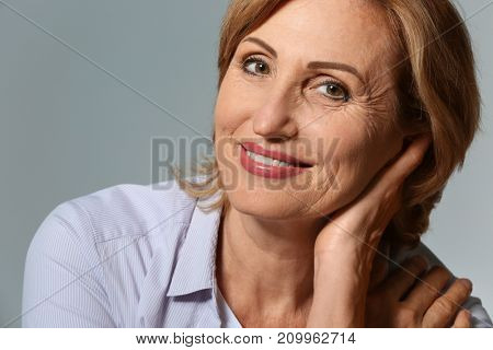 Beautiful mature woman on grey background