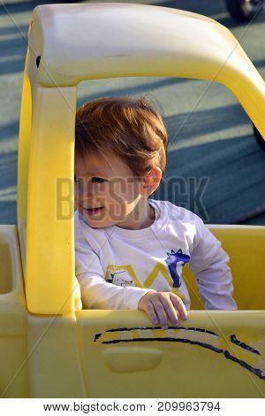 Playful little kid on plastic car toy.