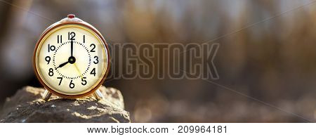 Time concept - red alarm clock standing on a stone - web banner with copy space