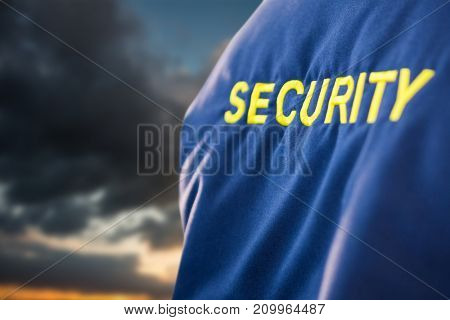 SECURITY text on uniform against blue and orange sky with clouds